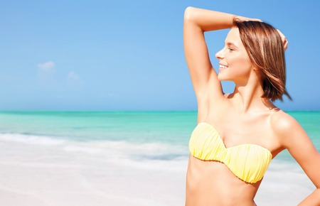 happy woman in bikini posing on summer beach photo
