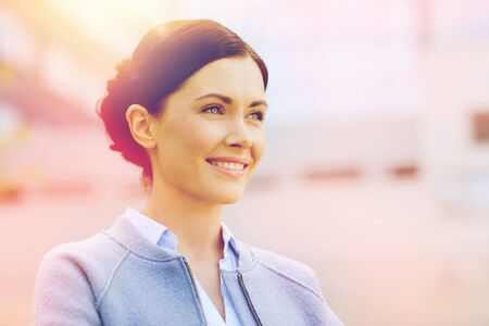 business and people concept - young smiling businesswoman over office building Stock Photo