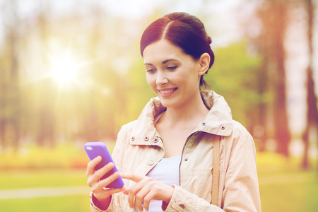 drinks, leisure, technology and people concept - smiling woman calling and talking on smartphone in park