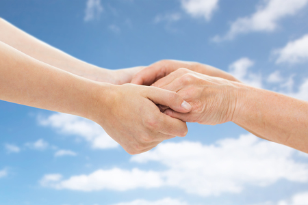 age, care and support concept - close up of senior woman and young woman holding hands over blue sky and clouds background
