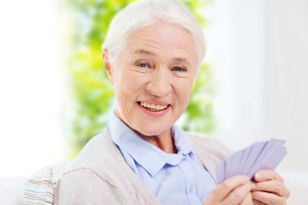 年齢、ゲーム、ギャンブル、火かき棒および人々 コンセプト - 年配の女性家でトランプを笑って幸せです 写真素材