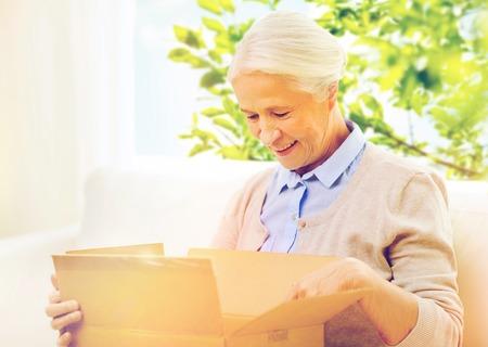 행복 한 고위 여자 집에서 소포 상자 스톡 콘텐츠