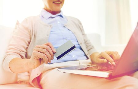 emoney: senior woman with laptop and credit card at home Stock Photo