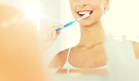 Femme à brosse à dents nettoyant les dents à la salle de bain Banque d'images - 79310402