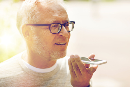 old man using voice command recorder on smartphone Stock Photo