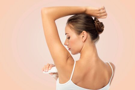 beauty, hygiene and people concept - beautiful young woman applying antiperspirant or stick deodorant over beige background Stock Photo