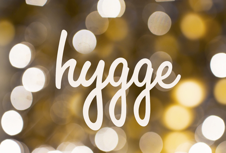 holidays and cosiness concept - word hygge over blurred golden lights background Stock Photo