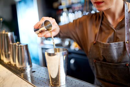 drinks, people and luxury concept - woman bartender with jigger pouring alcohol into shaker and preparing cocktail at bar counter