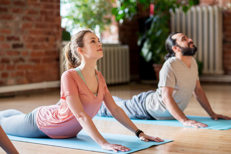 Fitness, personnes et mode de vie sain - homme et femme faisant cobra posent sur des tapis au studio de yoga Banque d'images - 79311837