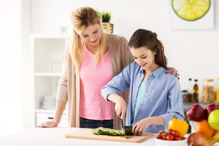 cooking food, healthy eating, family and people concept - happy mother and daughter chopping vegetables for dinner at home kitchen Stock Photo