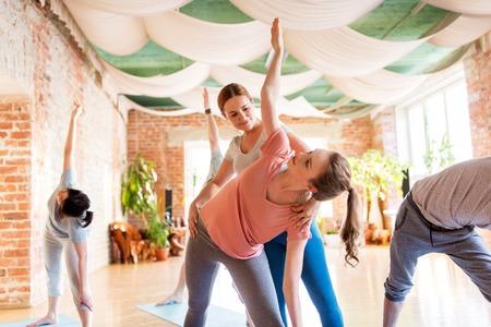 フィットネス、スポーツ、健康なライフ スタイル コンセプト - ジムやスタジオでマットでヨガの練習を行うパーソナル トレーナーを持つ人々 のグ
