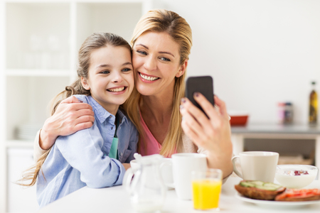 family, technology and people concept - happy mother and daughter with smartphone having breakfast and taking selfie at home kitchen