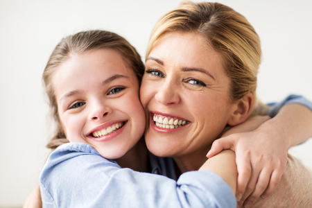 people and family concept - happy smiling girl with mother hugging