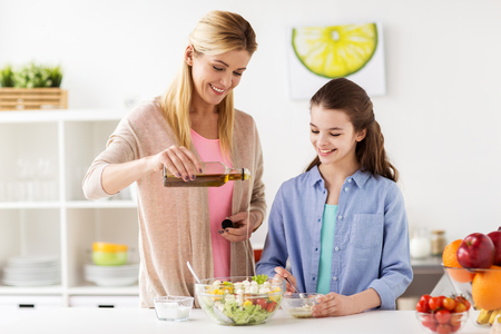 food, healthy eating, family and people concept - happy mother and daughter cooking and adding olive oil to vegetable salad for dinner at home kitchen Stock Photo