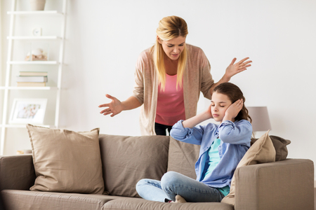 people, conflict and family concept - girl covering ears to not hear angry mother at home