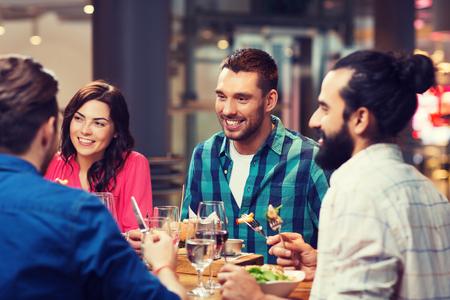Concepto de ocio, comida y bebida, personas y vacaciones - amigos felices cenando en el restaurante Foto de archivo - 79829212