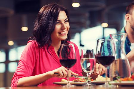 vrije tijd, voedsel en dranken, mensen en vakantieconcept - gelukkige vrouw met vrienden die diner hebben bij restaurant Stockfoto