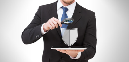 people, internet security and cyber protection concept - businessman holding magnifying glass over tablet pc computer with virtual antivirus program shield icon