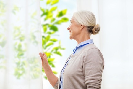 natural looking: age and people concept - happy smiling senior woman looking through window at home over green natural background Stock Photo