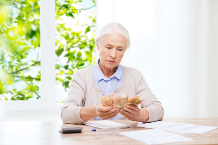 savings, age and people concept - senior woman with calculator and bills counting euro money at home over window and green natural background