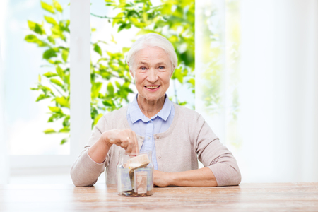 savings, annuity insurance and people concept - smiling senior woman putting money into glass jar at home over window and green natural background Stock Photo
