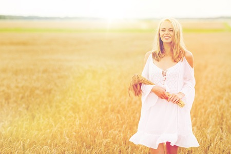 country, nature, summer holidays, vacation and people concept - smiling young woman in white dress with spikelets walking along on cereal field Stock Photo