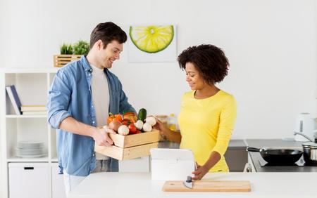 mensen, koken en gezond eten concept - gelukkige paar met doos met voedsel, groenten en tablet pc computer thuis keuken