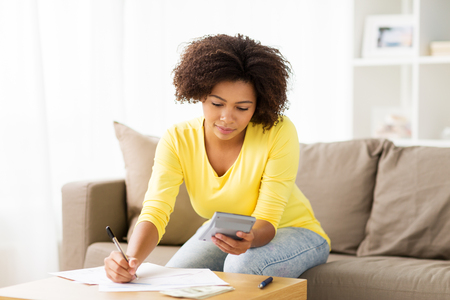 home finances: budget, finances and people concept - african american woman with papers and calculator counting money at home