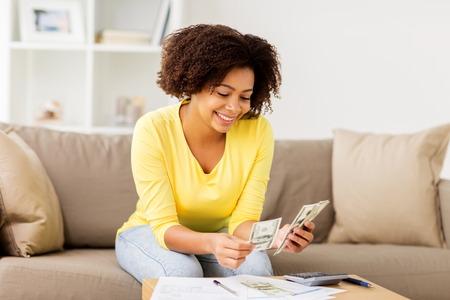 予算、財政および人々 のコンセプト - 論文と自宅でお金を数えて電卓アフリカ系アメリカ人女性と幸せ