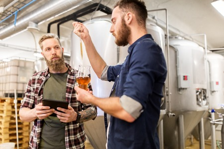 alcohol production, manufacture, business and people concept - men with pipette and tablet pc computer testing craft beer at brewery