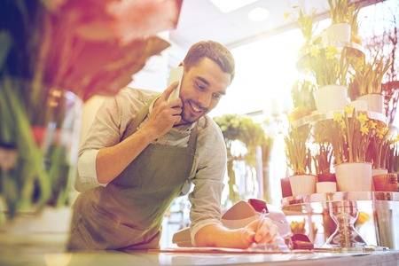 people, sale, retail, business and floristry concept - happy smiling florist man calling on smartphone and making notes to clipboard at flower shop counter Zdjęcie Seryjne - 79835142