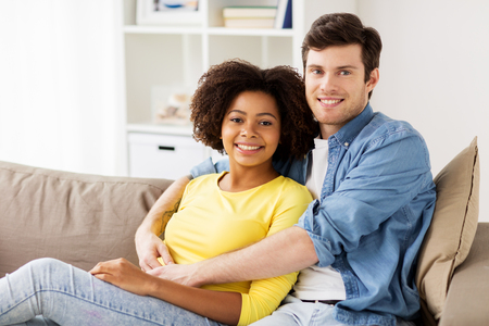relations, love and people concept - happy smiling international couple hugging at home