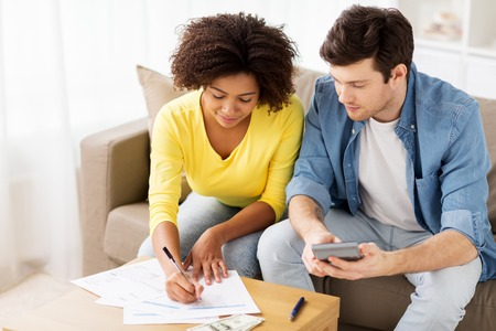 home finances: family budget, finances and people concept - couple with papers and calculator counting money at home Stock Photo