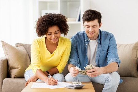 home finances: family budget, finances and people concept - happy couple with papers and calculator counting money at home