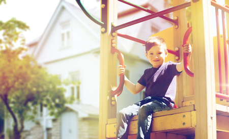 summer holidays, childhood and people concept - happy little boy on children playground climbing frame over house background