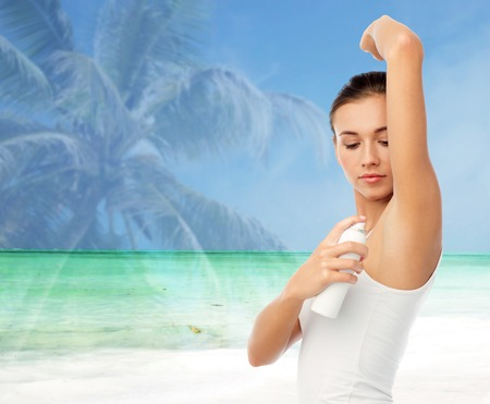 hygiene, bodycare and people concept - beautiful young woman applying antiperspirant or spray deodorant over exotic beach background with double exposure effect