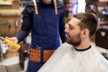 grooming, hairdressing and people concept - hairstylist showing hair styling spray to male customer at barbershop Stock Photo
