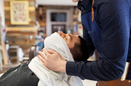 grooming, shaving and people concept - barber softening male face skin with hot towel at barbershop