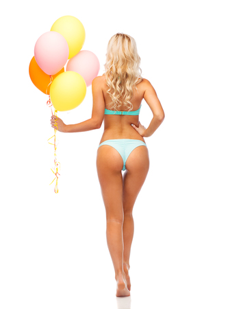 people, holidays and summer party concept - young woman in bikini swimsuit with air balloons from back over white background