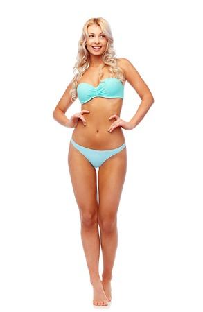 mensen, badkleding en de zomerconcept - gelukkige glimlachende jonge vrouw in bikinizwempak