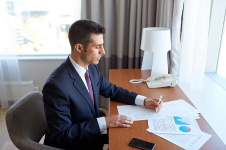 zakenreis, mensen en administratieconcept - zakenman met documenten die bij hotelruimte werken