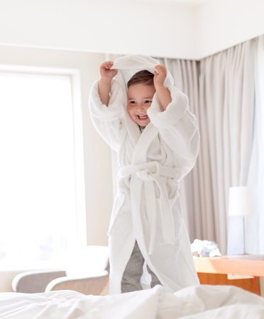 happy little boy in bathrobe on home or hotel bed
