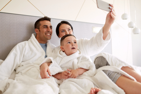 happy family with smartphone in bed at hotel room