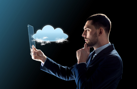 business, augmented reality and future technology concept - businessman in suit working with transparent tablet pc computer and cloud computing hologram over black background