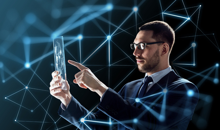business, augmented reality and future technology concept - businessman in glasses working with transparent tablet pc computer and virtual low poly shape projection over black background Foto de archivo