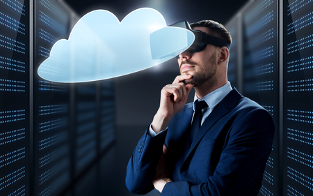 business, people and technology concept - businessman in virtual reality headset with cloud computing icon over futuristic server room background