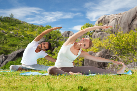 fitness, sport, relax and people concept - happy couple making yoga exercises sitting on mats outdoors over natural background Stock Photo