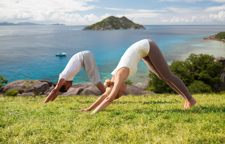 smiling couple making yoga exercises outdoors Standard-Bild