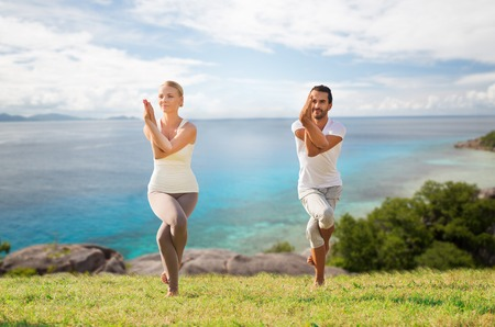 fitness, sport and people concept - smiling couple making yoga in eagle pose outdoors over natural background Stock Photo