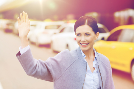 Lachende jonge vrouw met golvende hand over taxi Stockfoto